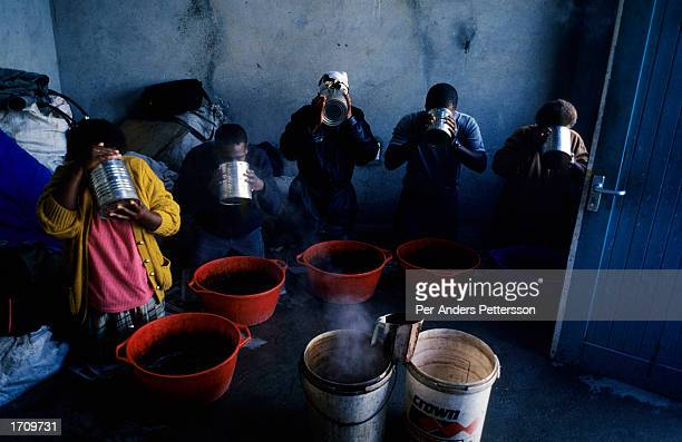 People drinking at home made brew at a traditional healers house on August 11, 2001 in Site C Khayelitsha, a township about 35 kilometers outside...