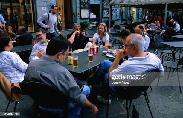 People drinking beer at outdoor tables.