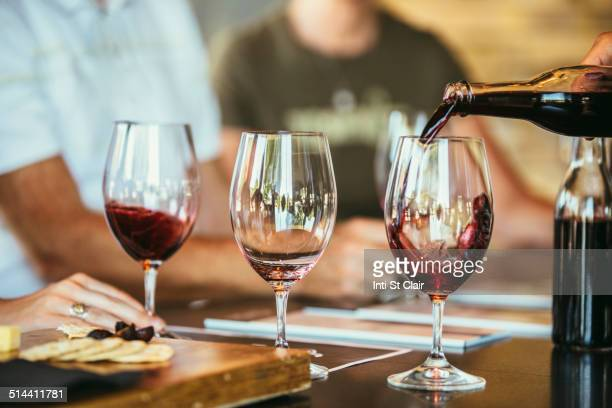 people drinking wine together in bar - wine tasting stock photos and pictures