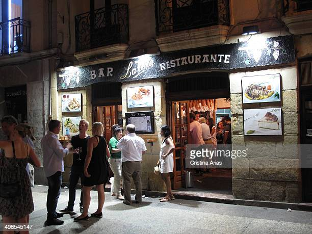 People drinking wines and tapas at the entrance to a bar in San Sebastian Guipuzcoa Basque Country Spain