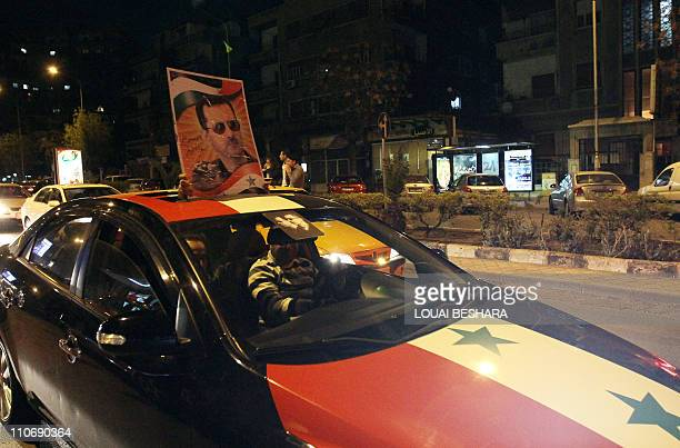 People drive a Syrian flag painted car, holding a portrait of Bashar al-Assad, early on March 23, 2011 in Damascus as security killed five and...