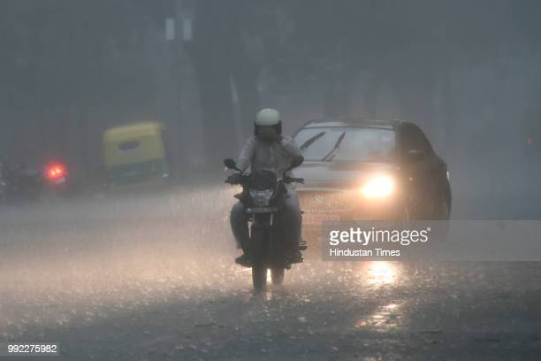 People drive amid heavy monsoon rain at KG Marg on July 5 2018 in New Delhi India