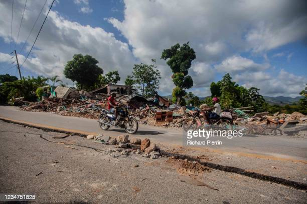 People drive by the damage after a 7.2-magnitude earthquake struck Haiti on August 18, 2021 in Marceline, Camp-Perrin, Haiti. Rescue efforts continue...