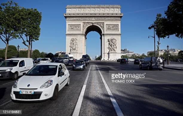 People drive their car down the Champs Elysee Avenue with the place de l'Etoile and the Arc de Triomphe on the background, on May 19, 2020 as France...