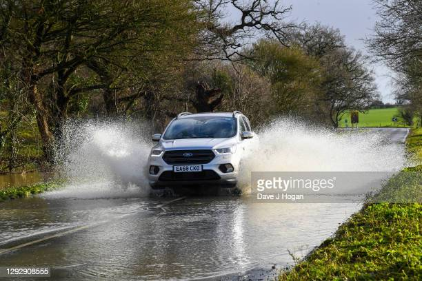 People drive through a flooded road following heavy rainfall on December 24, 2020 in Suffolk, United Kingdom .