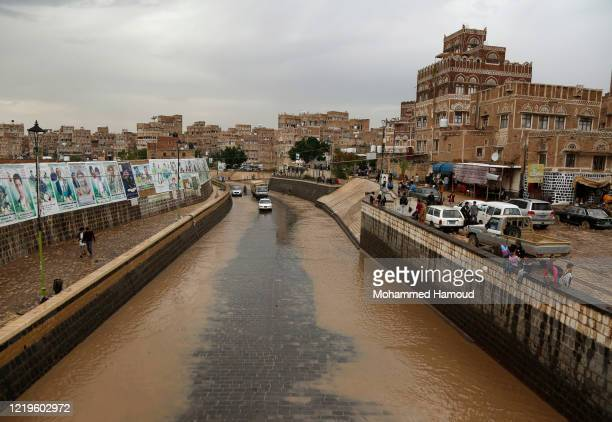 People drive through a flooded street after heavy rains on April 18 2020 in Sana'a Yemen