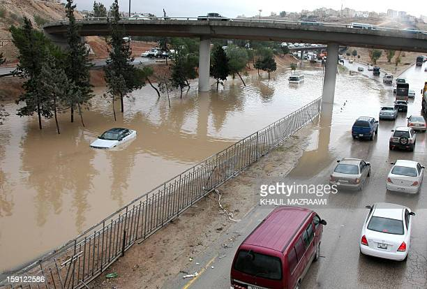 People drive through flooded streets in the Jordanian capital Amman on January 8 2013 Torrential rains swept through the desert kingdom for a second...