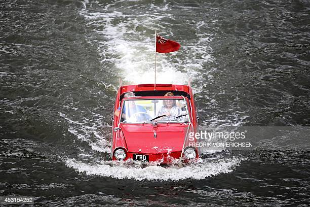 People drive with an amphibian vehicle in the river Mosel near TrabenTrabach southern Germany on August 3 2014 during the Amphib 2014 rally Fans of...