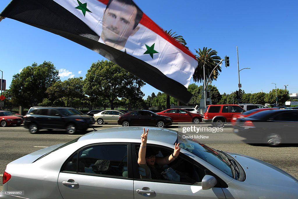 People driving by express their support as they pass a flag with a picture of Syrian president Bashar Hafez al-Assad at a rally to urge Congress to vote against a limited military strike against the Syrian military in response to allegations that Assad has used sarin gas to kill civilians on September 7, 2013 in Los Angeles, California. The Obama administration claims to have clear evidence that the Syrian military broke international law by killing nearly 1,500 Syrian civilians, including at least 426 children, in a chemical weapons attack on August 21, and is seeking the support of Congress for a missile strikes to prevent future chemical weapons attacks by the regime and other nations.