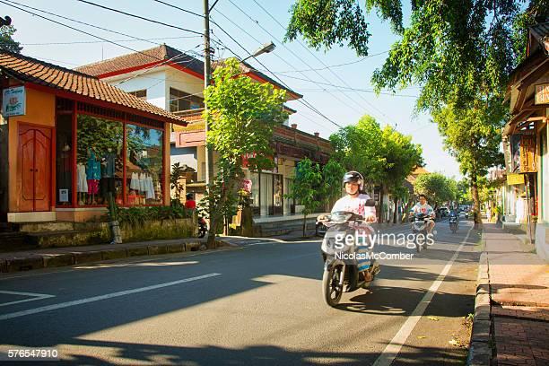 People driving their motorbikes through Ubud Bali