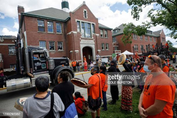 People drum and sing as a convoy of truckers and other vehicles travel in front of the former Kamloops Indian Residential School in support of the...