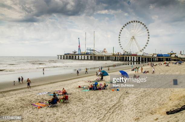 people during cloudy day at atlantic city beach - new jersey stock pictures, royalty-free photos & images