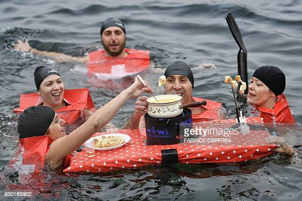 People eat a cheese fondue as they swim during the 78th Coupe de Noel swimming race in the Lake Geneva on December 18 2016 in Geneva More than 1800...