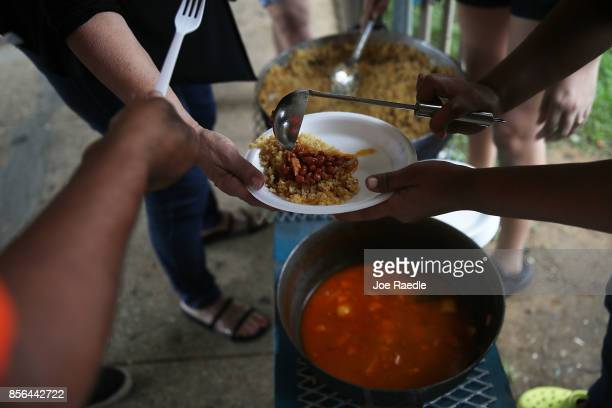 People eat a communal pot of food at the Torres de Francia complex as they deal with the aftermath of Hurricane Maria on October 1 2017 in San Juan...