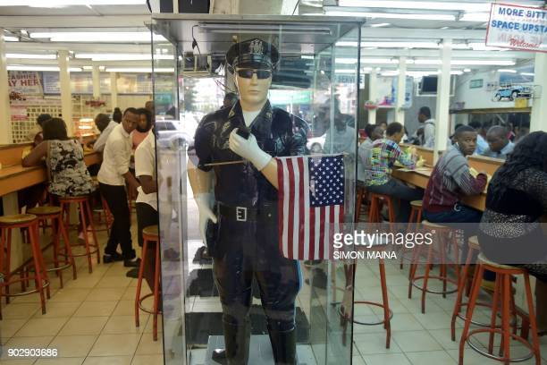 People eat and drink in a restaurant in downtown Nairobi with a mannequin wearing a US police uniform and carrying a flag as decoration on January 9...
