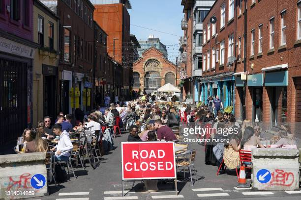 People eat and drink in the spring sunshine as pandemic lockdown restrictions ease in Manchester's Northern Quarter on April 23, 2021 in Manchester,...