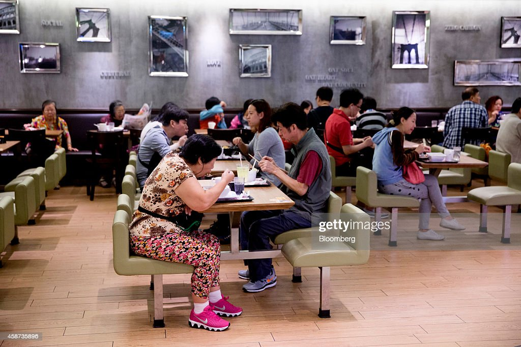 People eat and drink inside a restaurant at Lok Fu Plaza, operated by the Link Real Estate Investment Trust (REIT), in Hong Kong, China, on Monday, Nov. 10, 2014. The Link REIT, Asia's largest property trust which owns neighborhood malls, food markets, and car parks, is scheduled to announce interim results on Nov. 13. Photographer: Brent Lewin/Bloomberg via Getty Images