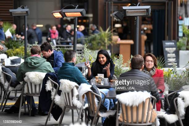 People eat and drink while sitting at tables outside a restaurant at lunchtime in the City of London on April 29, 2021. - Britain has been the...