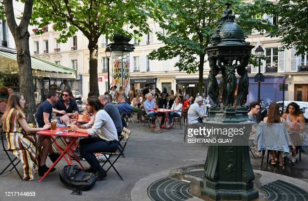 People eat and have drinks on restaurant and cafe terraces in Paris on June 2 as cafes and restaurants reopen in France with the easing of lockdown...