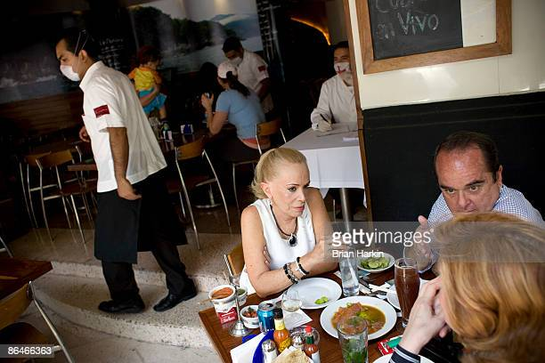 People eat at a restaurant in the Condesa neighborhood as a employee wears a protective mask on May 6 2009 in Mexico City Mexico The government on...