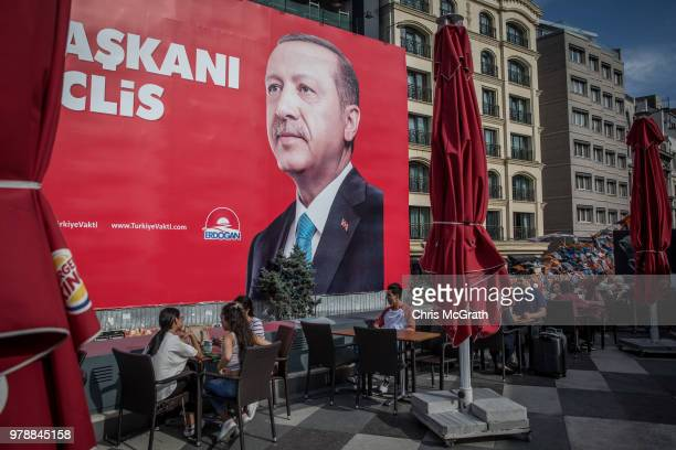 People eat at Burger King underneath an election poster showing the portrait of Turkey's President Recep Tayyip Erdogan on June 19 2018 in Istanbul...