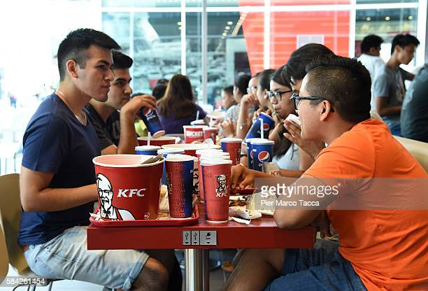 People eat at KFC restaurant in Milan during the opening of a new Kentucky Fried Chicken branch on July 28 2016 in Milan Italy KFC Milan seats 160...