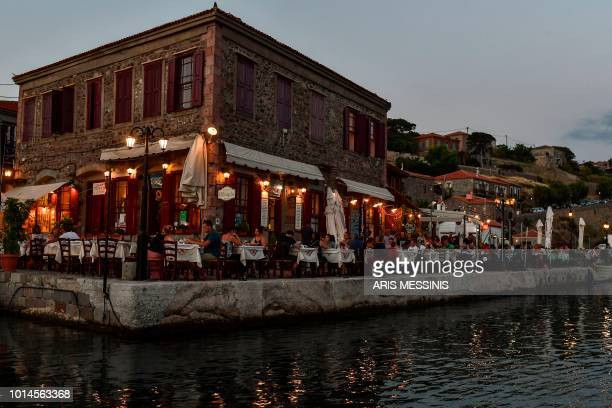 People eat at restaurants at the port of Mithymna in the northeastern island of Lesbos on August 3 2018