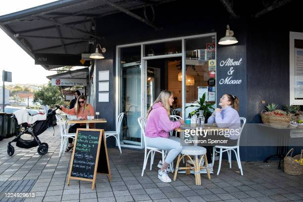 People eat breakfast at Albert and Moore Cafe in Freshwater on May 15, 2020 in Sydney, Australia. Restrictions put in place in response to the...