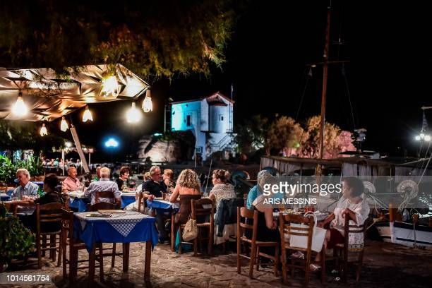 People eat dinner at a tavern on the small port of the village of Skala Sykamineas in the northeastern island of Lesbos on August 3 2018