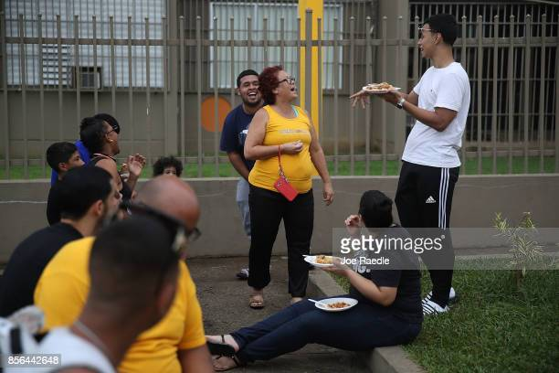 People eat dinner together at the Torres de Francia complex as they deal with the aftermath of Hurricane Maria on October 1 2017 in San Juan Puerto...