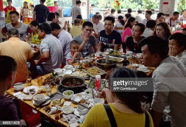 People eat dog meat at a restaurant in Yulin, in China's southern Guangxi region on June 21, 2017. China's most notorious dog meat festival opened in...
