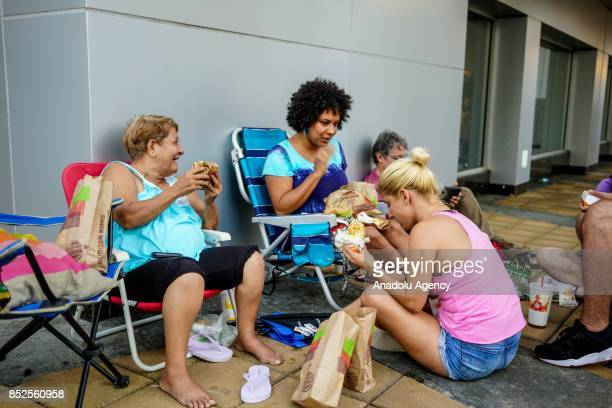 People eat fast food and charge their devices after Hurricane Maria at Milla de Oro in Hato Rey Puerto Rico on September 23 2017 The banking district...