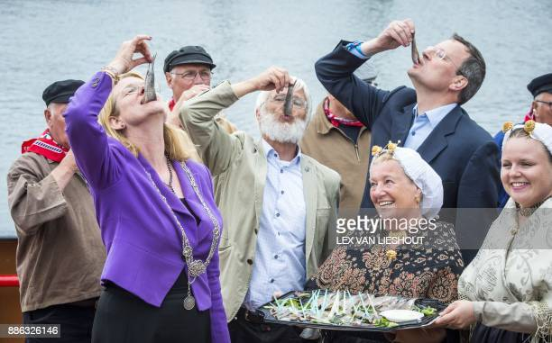 People eat herring during the 70th edition of the Vlaggetjesdag on June 16 2017 in Scheveningen to celebrate the new herring season Two disgruntled...