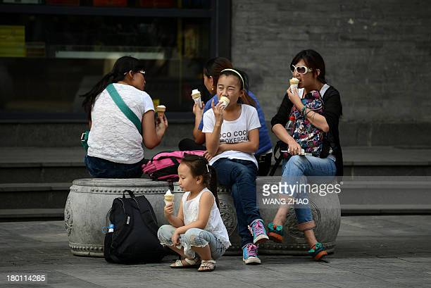 People eat ice cream as they sit on stone seats along a business street in Beijing on September 9 2013 Chinese inflation slowed to 26 percent...