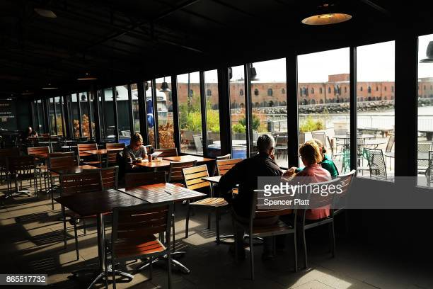 People eat in a cafe in Red Hook Brooklyn on October 23 2017 in New York City Red Hook like many coastal neighborhoods in New York was severely...