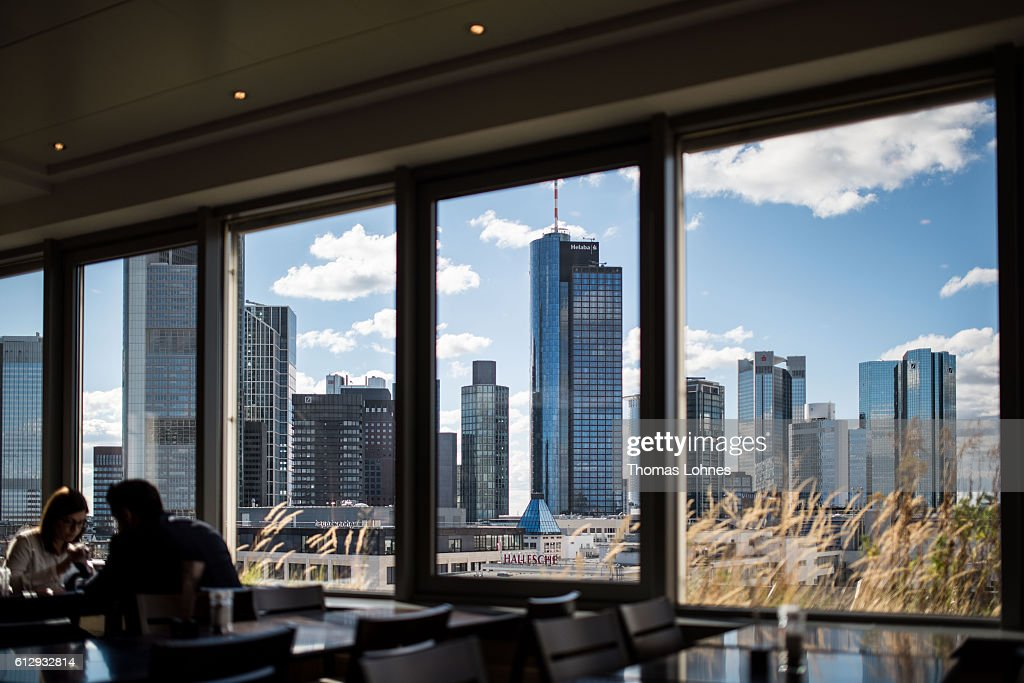 People eat in a restaurant with the view to the finance district of Frankfurt on October 5, 2016 in Frankfurt, Germany. Banks across Europe are struggling as their profits have fallen amid an ongoing period of low interest rates, and many, including Commerzbank and Deutsche Bank of Germany, ING and ABN Amro of Holland, and Banco Popular of Spain, are responding by slashing thousands of jobs in an effort to cut costs.