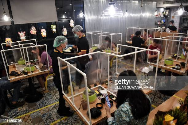 People eat in between plastic partitions, set up in an effort to contain any spread of the COVID-19 coronavirus, at the Penguin Eat Shabu hotpot...