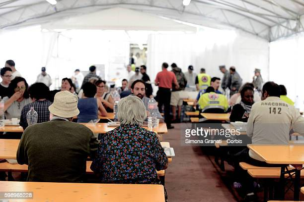 People eat in the canteen area of the tent camp erected for earthquake victims on August 31, 2016 in Arquata del Tronto, Italy. The region was struck...