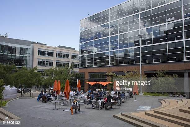 People eat lunch in a courtyard outside of the Amazoncom Inc headquarters in the South Lake Union neighborhood of Seattle Washington US on Wednesday...