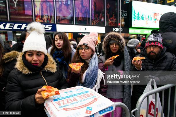 People eat pizza as they arrive to celebrate New Years eve in Times Square on December 31 2019 in New York City Because of the mild weather a larger...
