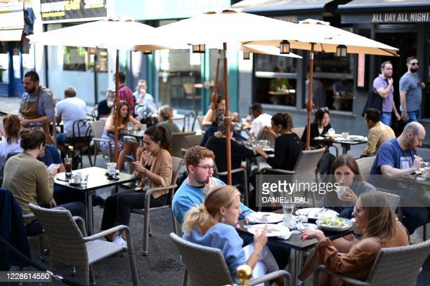 People eat sunday lunches at tables outside a cafe in Soho, in London on September 20, 2020 as the British government consider fresh nationwide...