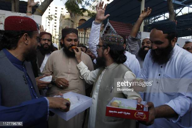 People eat sweets to celebrate Pakistani fighter jets shooting down two Indian aircrafts in Karachi Pakistan on Wednesday Feb 27 2019 As Asia's most...