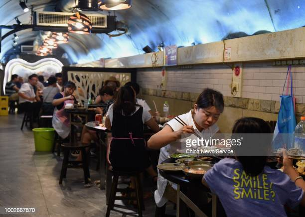 People eat the hot pot at an airraid shelter to escape the summer heat waves on July 17 2018 in Chongqing China The temperature reached 37 degrees...