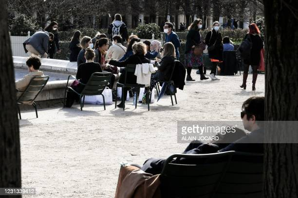 People eat their lunch and enjoy the sunny weather during a break outside in the gardens of the Palais Royal gardens, in Paris, on February 23, 2021.