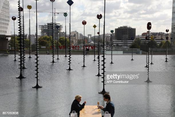 People eat their lunch at the La Defense business district in Courbevoie on October 3 2017 / AFP PHOTO / LUDOVIC MARIN
