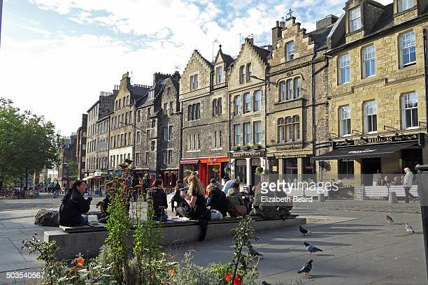 People eat their lunch outside near the flower garden marking the former site of the gallows of Grassmarket, Edinburgh, on a warm autumn day.