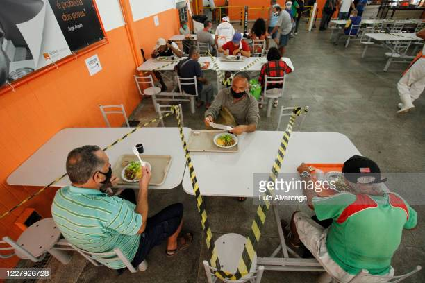 People eat their meals while maintaining social distance at a popular soup kitchen on August 5, 2020 in Niteroi, Brazil. Employees received special...