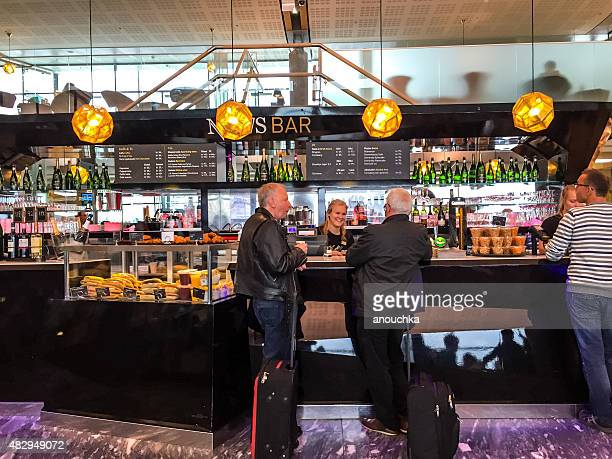 People eating and drinking at News Bar, Oslo Airport, Norway