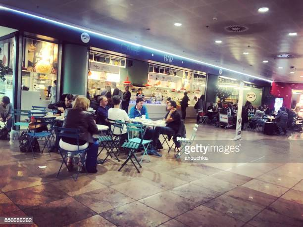 People eating and drinking before flights in a cafe inside  Brussels Airport, Belgium