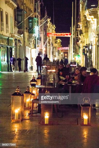 people eating and drinking outside restaurant on the streets of old town valetta, malta - valletta stock pictures, royalty-free photos & images
